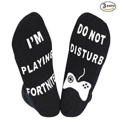 """Black socks with white lettering that says """"i'm playing Fortnite"""" on one foot and """"do not disturb on the other foot"""". Funny gift idea and great for a stocking stuffer, too"""